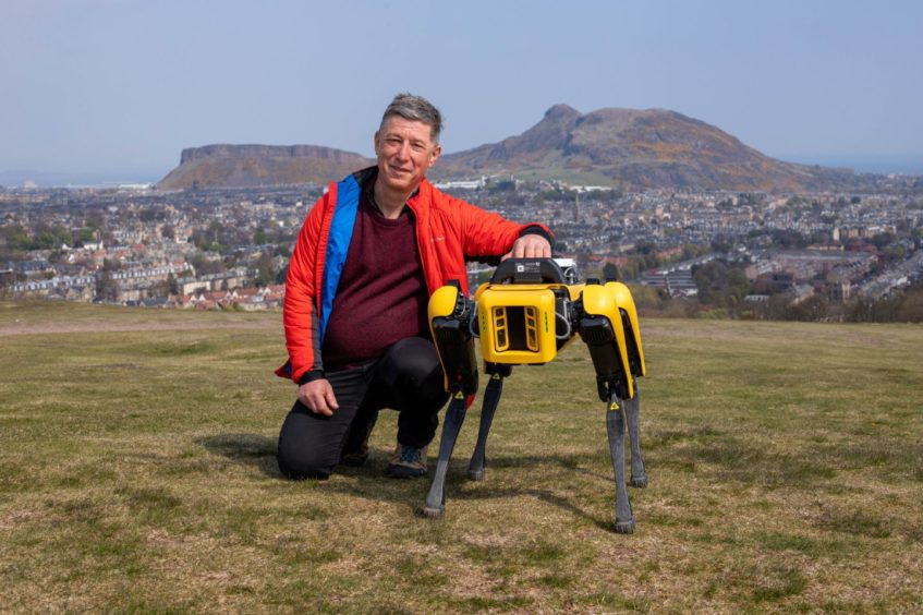"""Undated handout photo issued by Heriot-Watt University of Prof Yvan Petillot with a four-legged robot """"dog"""" which is helping scientists in Scotland research how the machines can help people working in hazardous environments such as oil platforms and refineries, on Blackford Hill, Edinburgh. Heriot-Watt University/PA Wire"""