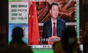 A news report on Chinese President Xi Jinping's New Year's Eve speech is shown on a public screen in Hong Kong, China, on Thursday, Dec. 31, 2020. Photographer: Roy Liu/Bloomberg