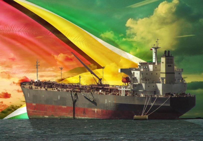 The oil tanker on the ocean with Guyana flag background; Shutterstock ID 1553276936; purchase_order: Energy Voice; job: To go with Brian Wilson column in EV supplement; 80b95484-4973-4158-a6ca-1c9cfeacaa48