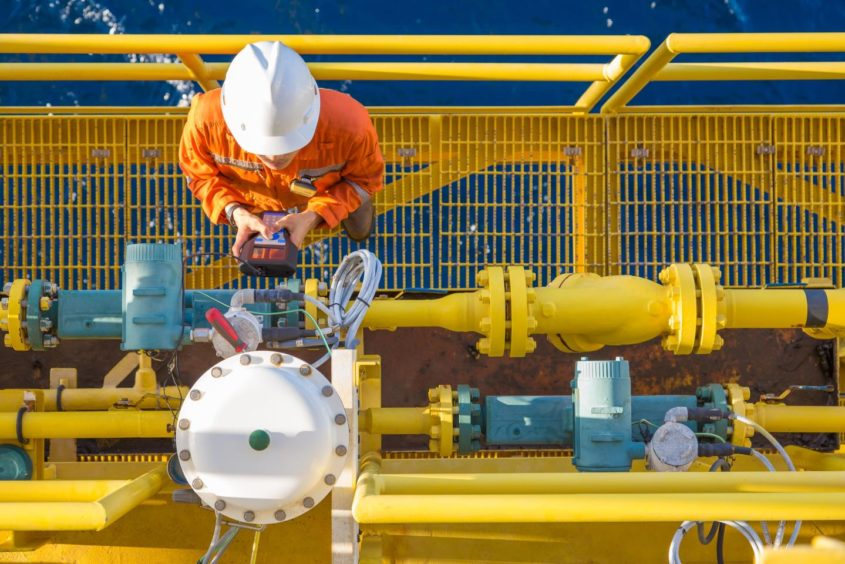 A technician checking equipment on an offshore oil and gas platform.