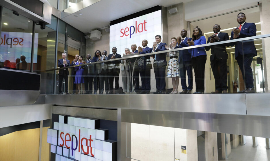 Group of people in suits clap while standing on a shiny balcony