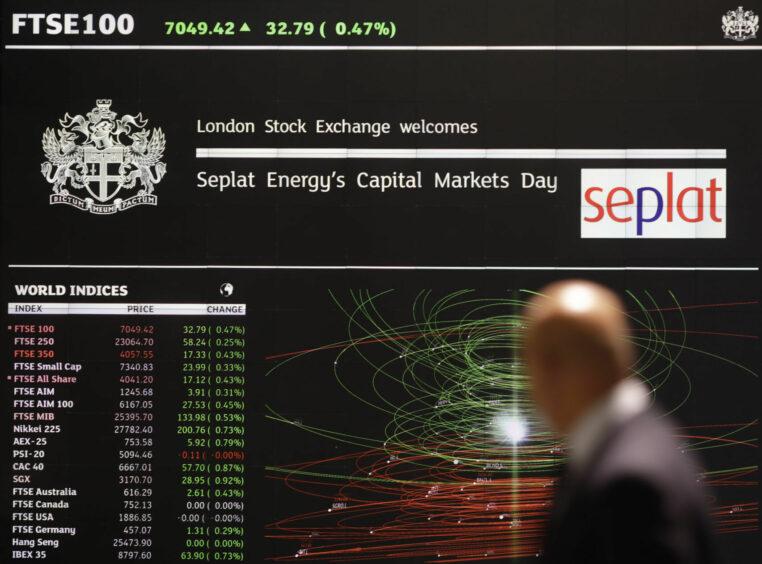 Man in suit walks past London Stock Exchange board on Seplat