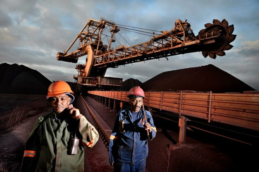 Two workers walk past coal mining equipment