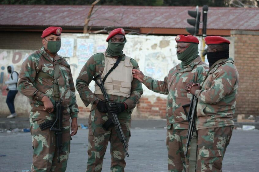 Four soldiers wearing masks in a South African settlement