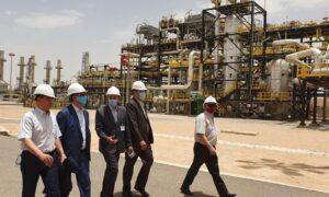 Men in hard hats walk past industrial machinery