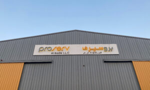 A warehouse with a sign in English and Arabic
