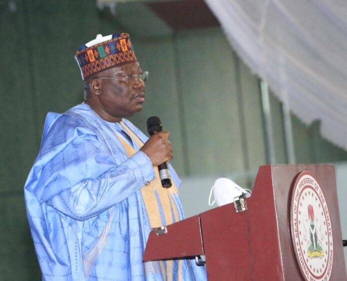 Man in Nigerian robes stands at podium