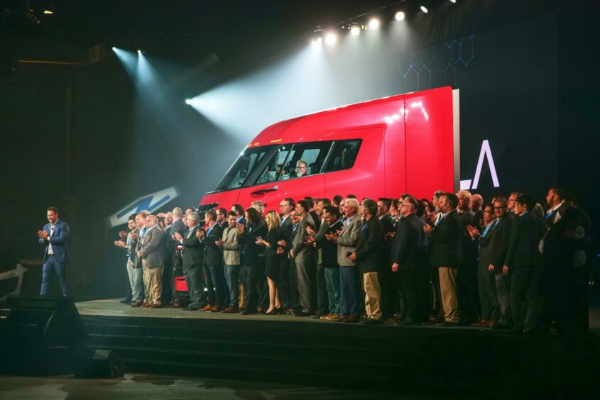Truck on a stage with clapping people in foreground