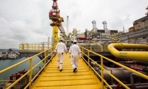 Workers walk along an elevated walkway on the Tullow Oil Plc Prof. John Evans Atta Mills Floating Production Storage and Offloading (FPSO) vessel docked at the Sembcorp Marine Tuas shipyard in Singapore, on Thursday, Jan. 21, 2016.  Photographer: Nicky Loh/Bloomberg