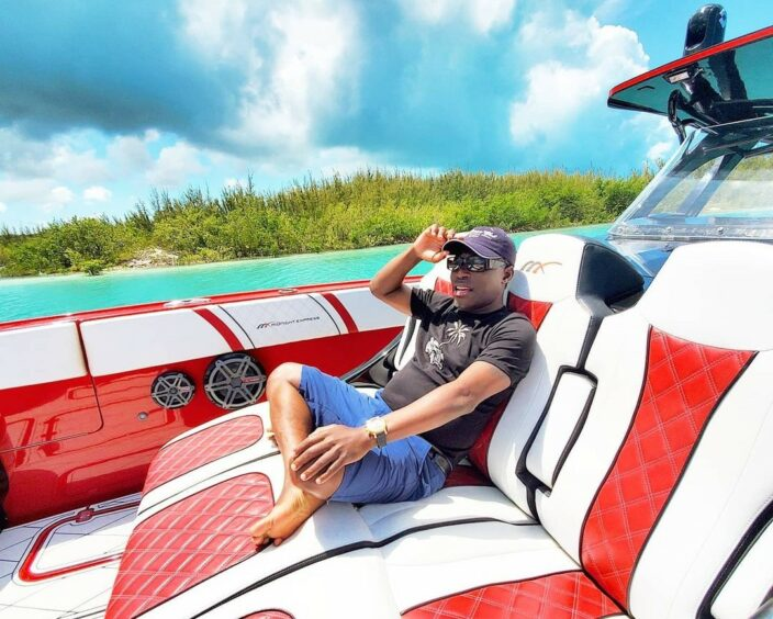 Man reclines in a speedboat under a blue sky
