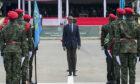 Man in suit stands between soldiers in red berets