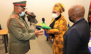 Man in military uniform receives flag from woman in yellow dress