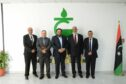 Five men stand in front of giant green logo with Libyan flag to the right