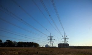 Electricity transmission pylons stand in front of Sizewell A, right, and B, left, nuclear power stations, operated by Electricite de France SA (EDF), stand in Sizewell, U.K., on Friday, May 15, 2020. The network operator struck a deal with EDFto cut supply at itsSizewellnuclear plant by half for at least six weeks because the demand for power is 20% lower than normal as measures to contain the coronavirus have shut industry and kept people at home for weeks.