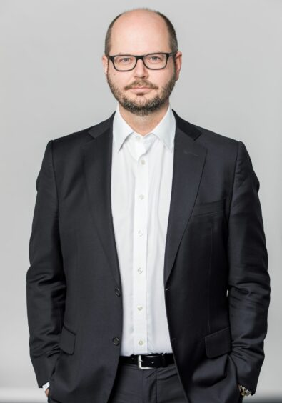 Man with glasses wears jacket
