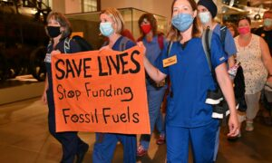 People in scrubs holding anti-fossil fuel sign