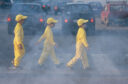Three children in yellow overalls cross a cloudy road