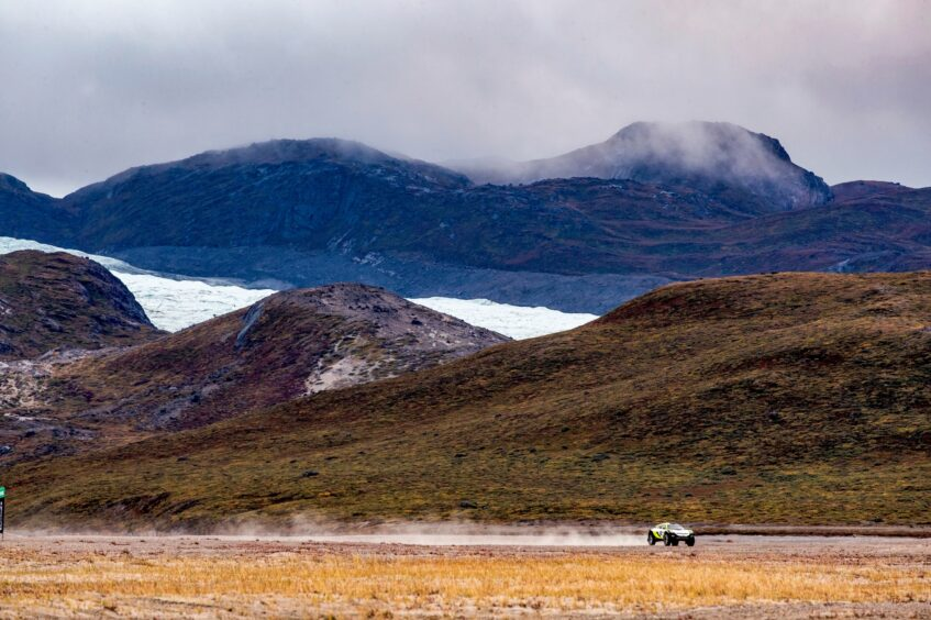 SUV races across big landscape with mountains and clouds behind