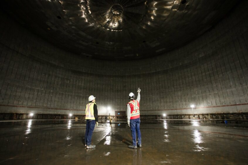 Two men stand inside massive tank pointing upwards