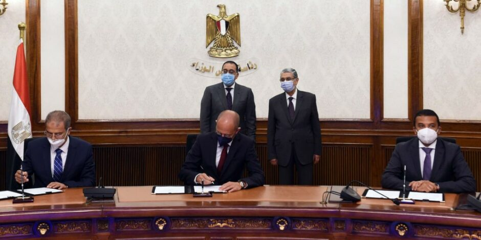 Men sign document at table in front of Egyptian arms