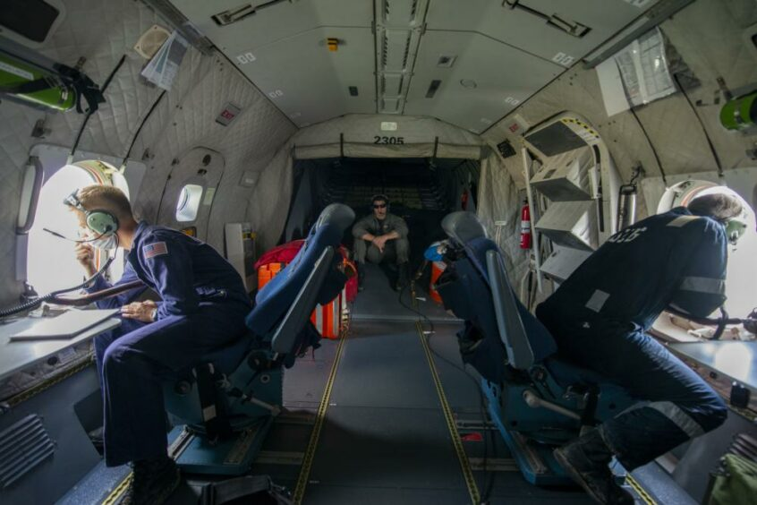 Inside of an aeroplane, with people in overalls peering out of windows