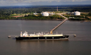 An LNG carrier docked at the end of a long jetty