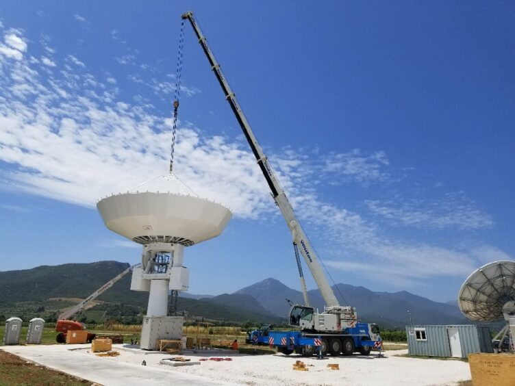 A crane lowers a satellite dish against a blue sky