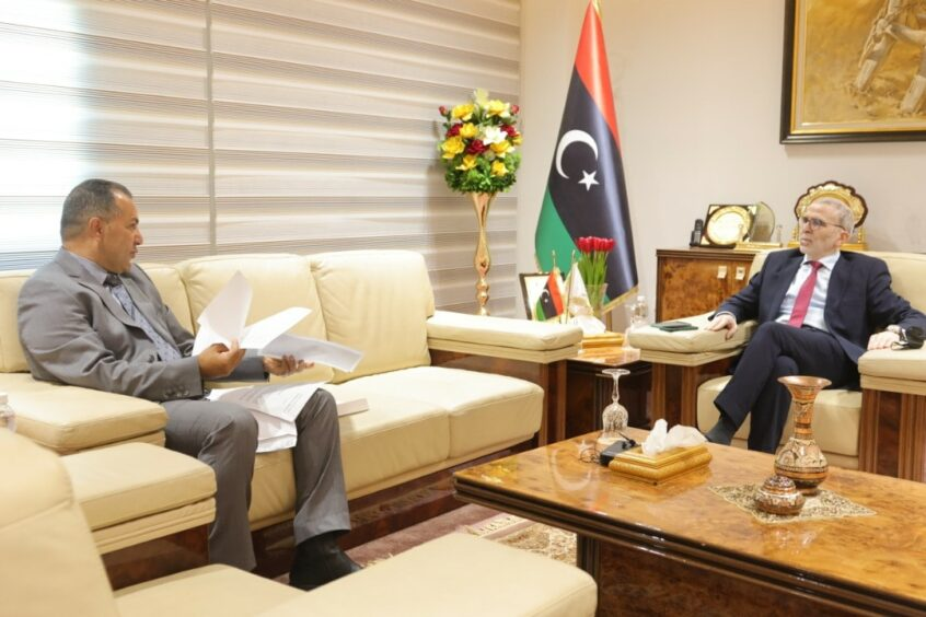 Two men sit on sofas with a Libyan flag behind