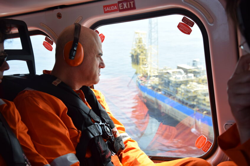 Man in headphones looks out of helicopter at big ship