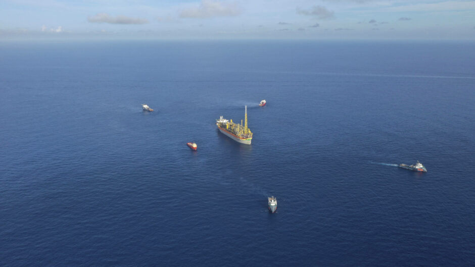 A vessel surrounded by smaller ships in the blue ocean