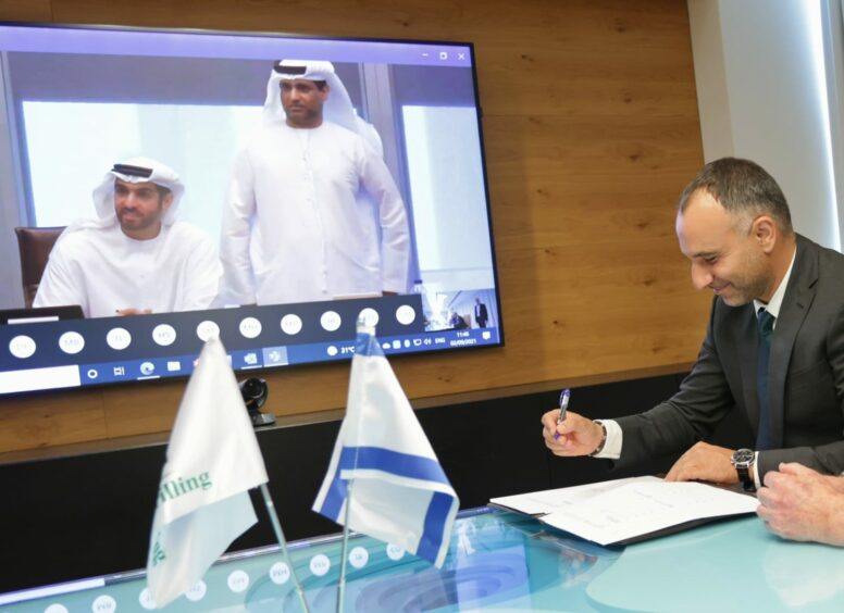 Two men on screen and one to right signing document, with little flags on table