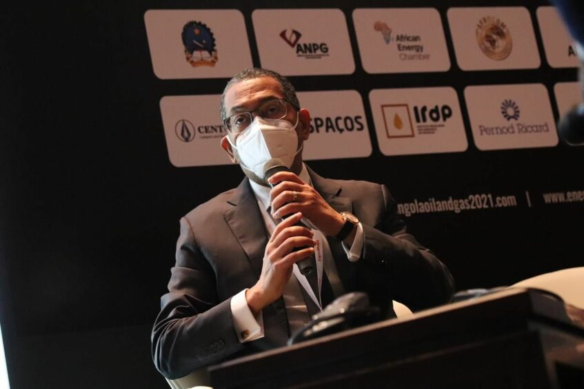 Man in a mask speaks into a mic in front of company logos
