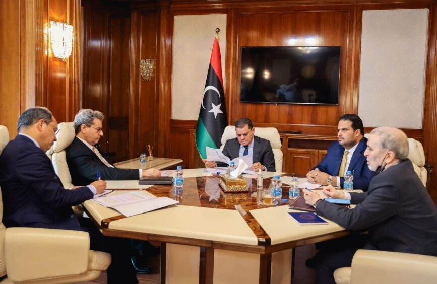 Men sit round a table in front of Libyan flag