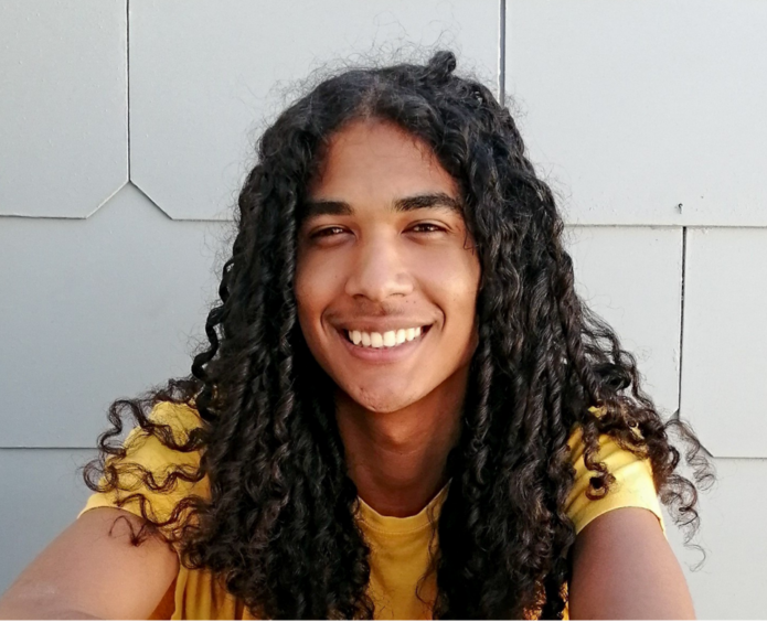 Man with long hair smiles