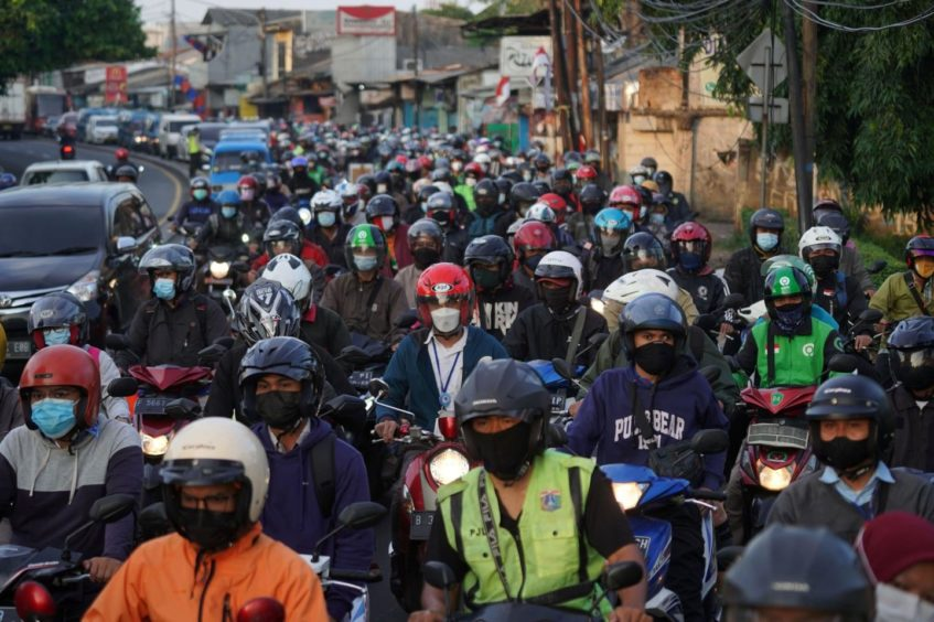 Motorcyclists wait at a checkpoint in Jakarta, Indonesia, on Wednesday, Aug. 4, 2021. Southeast Asia's largest economy has been topping the world's tally of daily Covid-19 deaths as the delta variant spreads through the country and overwhelms its hospitals.