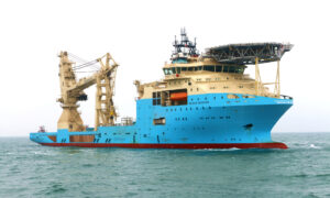 A big blue ship in the sea, with cranes on the back