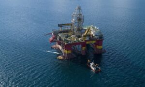 A drilling rig in a deep blue sea with a smaller vessel in front