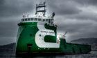 A green ship under dark clouds