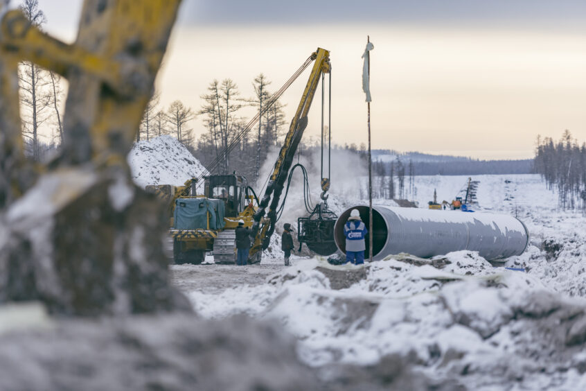 Snowy landscape with yellow diggers and workers
