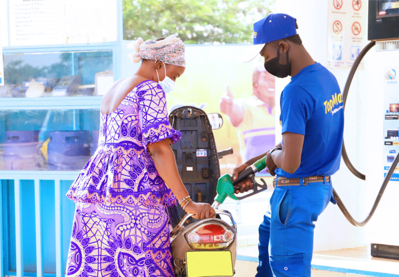 Filling up tanks at a service station, a man in a blue uniform helps