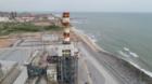 Power plant stripey chimney next to sea shore