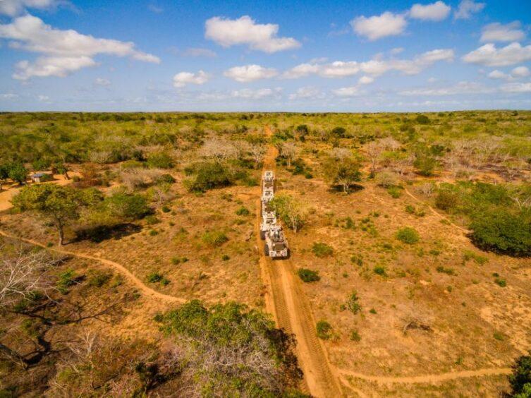 Seismic trucks drive across an orange landscape with scrubby brush