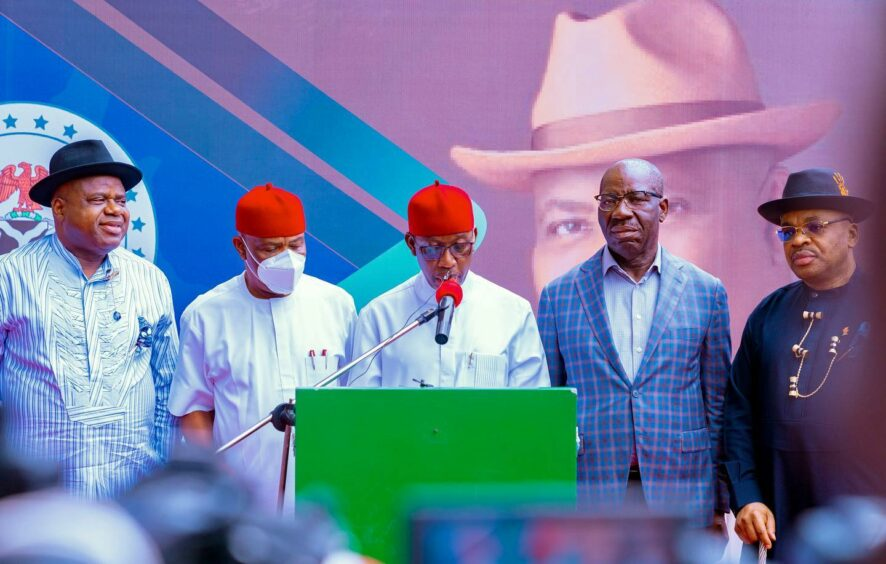 Men stand at a podium, one with a red hat speaks into a mic