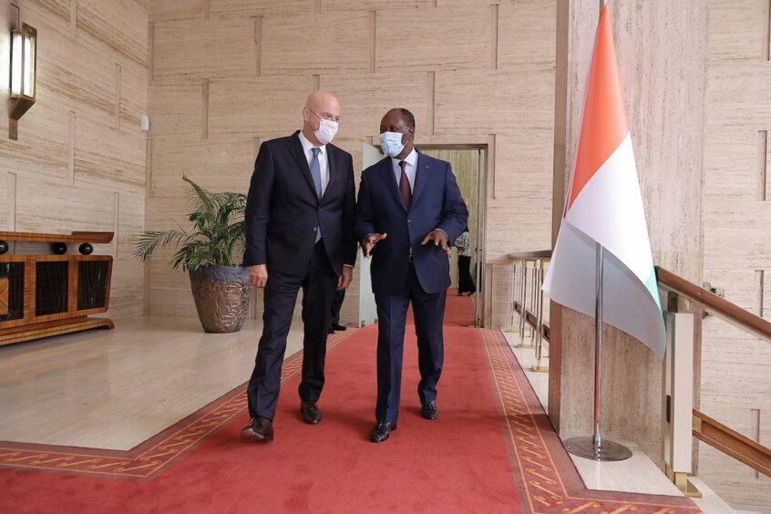 Two men walk along talking while wearing masks on a red carpet