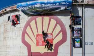 Climbers attach a banner to the top of an oil tank over a Shell logo