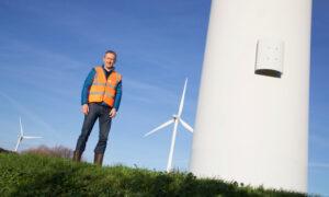 Man in orange vest stands next to wind turbine