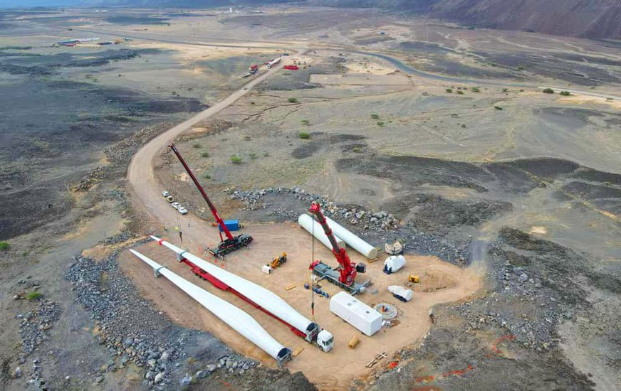 Two cranes move wind turbine blades in an aerial shot