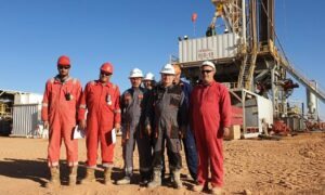 Men in overalls in front of a drilling rig