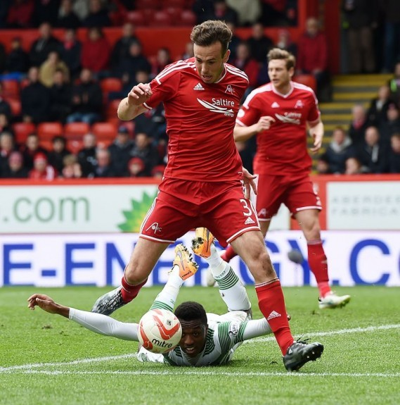 Cries for a penalty can be heard as Aberdeen's Andrew Considine takes down Darnell Fisher (below) in the box