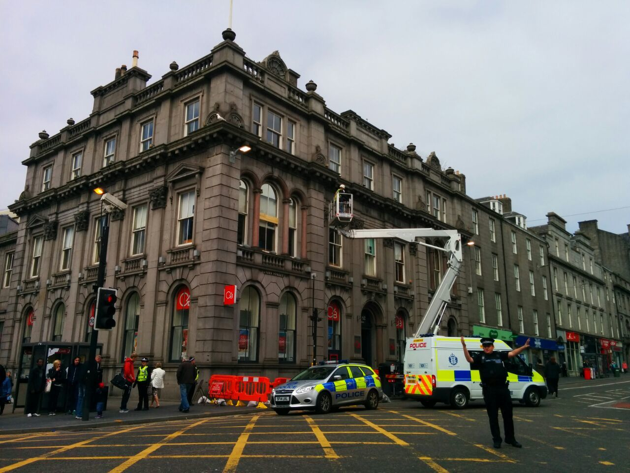 Police officers redirect traffic around the Clydesdale bank as workers check the building.